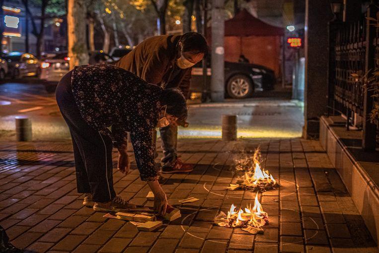 Inwoners van Wuhan verbranden tijdens de jaarlijkse viering van Qingming papieren bankbiljetten ter nagedachtenis van de coronadoden. Beeld EPA