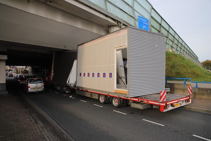 De vrachtwagen kwam klem te zitten onder het viaduct.