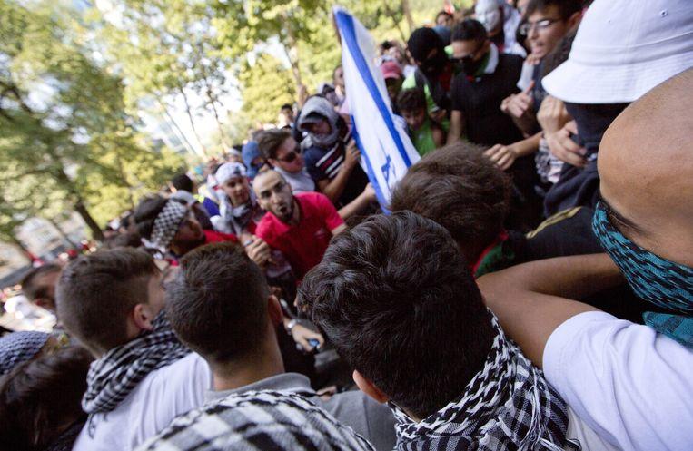 De Israëlische vlag wordt door deels gemaskerde demonstranten in brand gestoken. Beeld AP