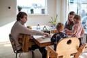 Het gezin speelt een spelletje aan tafel, met Elias in Wessels armen.