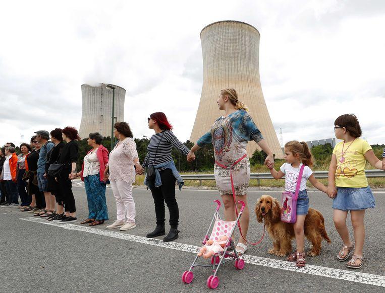 Mensen staan hand in hand als vorm van protest tegen de Belgische kerncentrale in Tihange. De deelnemers aan de 90-kilometerlange mensenketting willen dat de kerncentrale gaat sluiten.  Beeld ANP