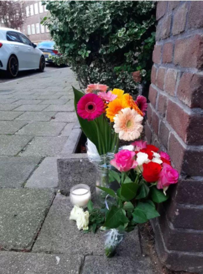Bloemen bij de ingang van het woongebouw waar de dode vrouw werd gevonden.