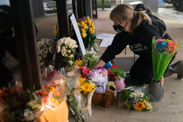 Een vrouw legt bloemen neer aan een van de massagesalons waar gisteren vier personen werden doodgeschoten in Atlanta. Beeld AFP
