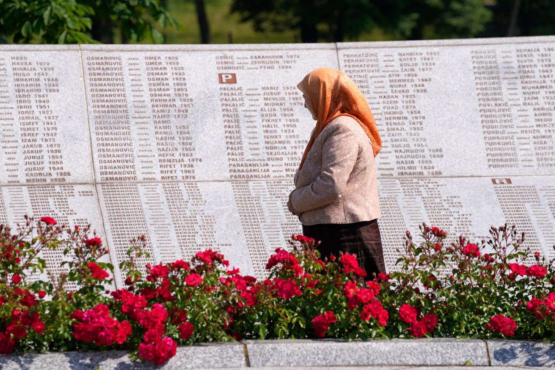 Een vrouw leest de namen op het monument voor de slachtoffers van de genocide op Bosnische moslims, op de begraafplaats van Potocari, in de buurt van Srebrenica. Beeld AP
