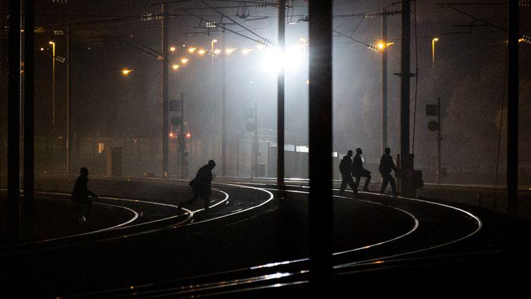 Vluchtelingen wandelen over de treinsporen in de buurt van de Eurotunnel in Calais