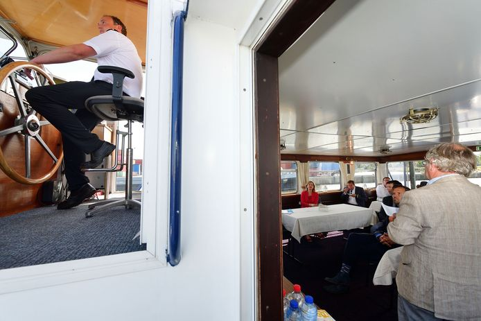 Terwijl demissionair minister Cora van Nieuwenhuizen luistert naar de Roosendaalse wethouder Cees Lok, vaart de schipper het gezelschap door de Theodorushaven.
