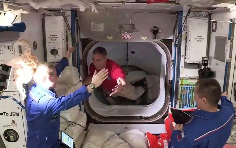 Astronaut Mike Hopkins van SpaceX wordt bij aankomst in het ISS begroet door astronaut Kate Rubins. Beeld AP