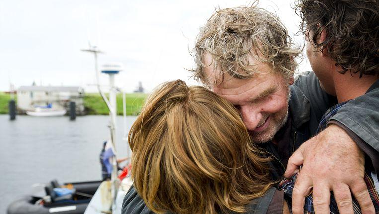 Zeezeiler Henk de Velde omhelst zaterdag zijn zoon (R) en de vriendin van zijn zoon (L) na aankomst in IJmuiden. De zeiler vertrok in 2007 voor zijn Never Ending Voyage. Beeld anp