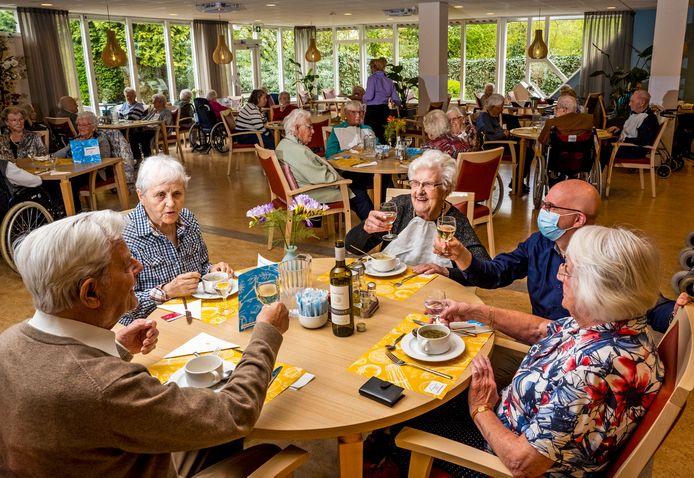 Bewoners kunnen weer samen eten en het glas heffen in verpleeghuis Vaartland in Vlaardingen. In het midden zit mevrouw Meertens (100). Tegenover haar Aad Kamp (91), naast haar (met mondkapje) zorgmanager Jos de Lang.