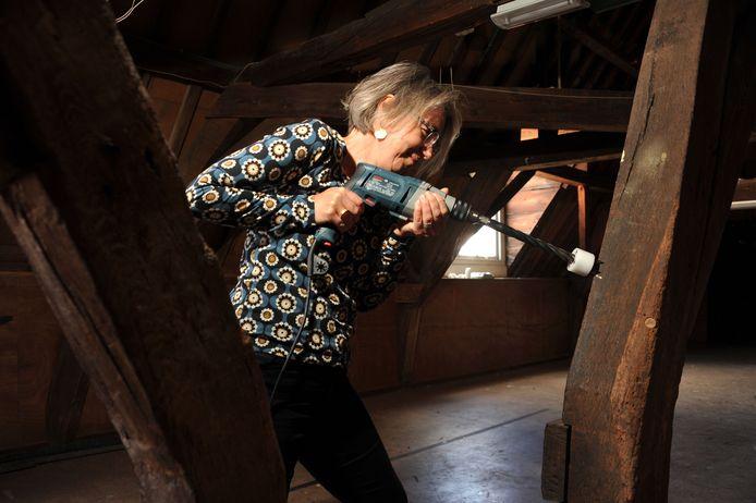 Bouwhistoricus Christine Weijs boort in eeuwenoude balken om de ouderdom van panden te kunnen vaststellen.
