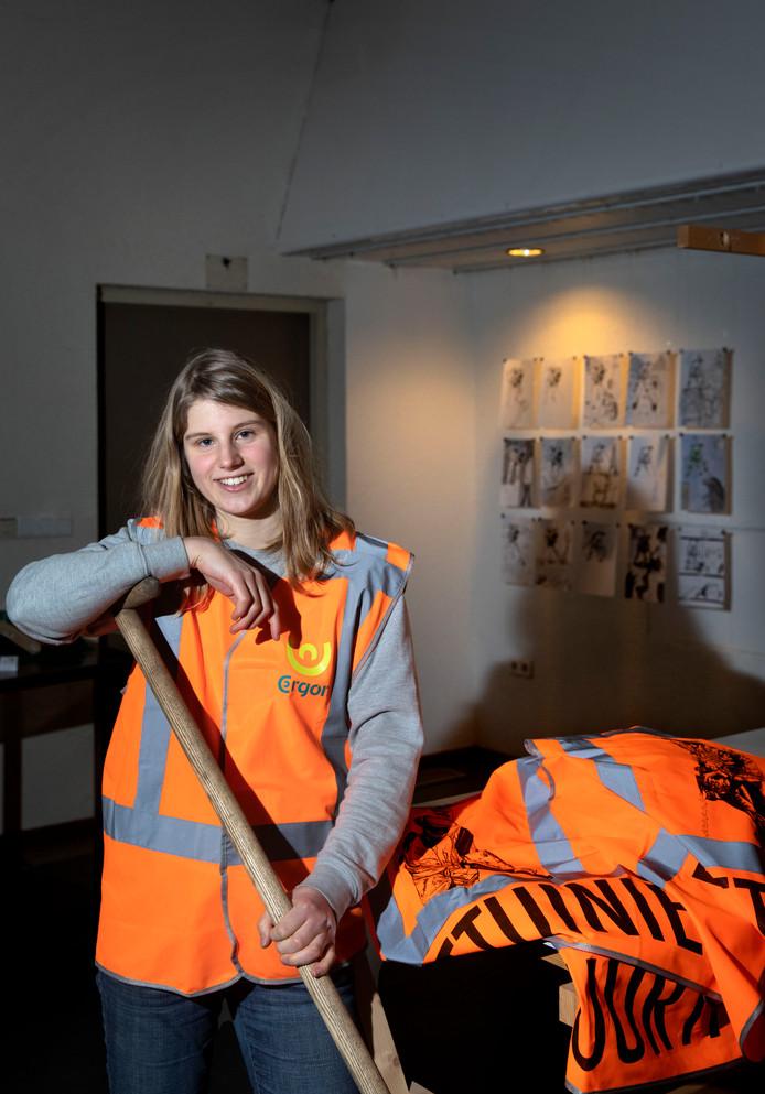 Cécile Espinasse met schoffel en een aantal van de hesjes die zij maakte  als afstudeeropdracht van de Design Academy Eindhoven.