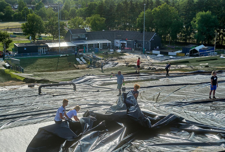 Vrijwilligers bezig met het herstel van de afgebrande skibaan  De Schans in Uden. In de achtergrond het clubhuis van de skiclub.
