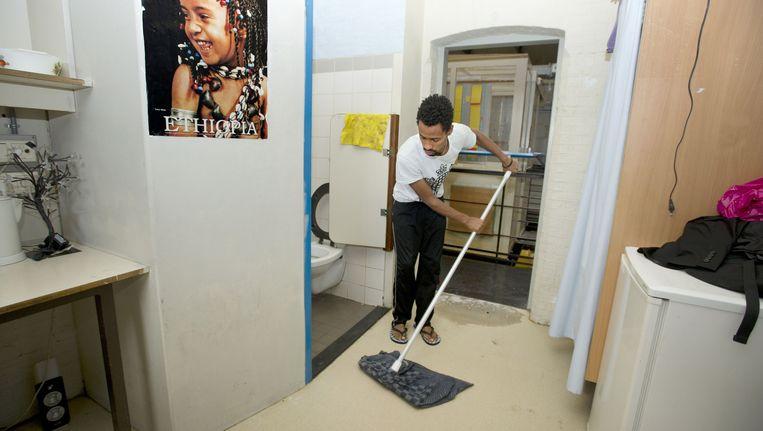 Een uitgeprocedeerde asielzoeker maakt zijn kamer schoon in de Vluchthaven. Beeld anp