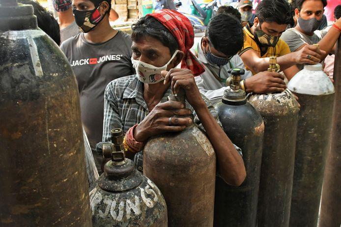 Familieleden van coronapatiënten in de rij om zuurstofvoorraden aan te vullen in New Delhi.
