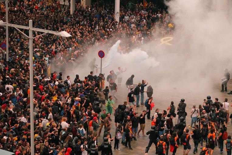 De politie probeert de betogers in bedwang te houden aan de luchthaven El Prat in Barcelona. Beeld AFP
