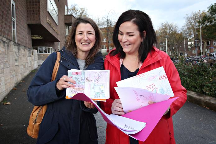 De Gorcumse leerkrachten Anna Maarse (links) en Saskia van Willigen overhandigen kindertekeningen aan PABO studenten.