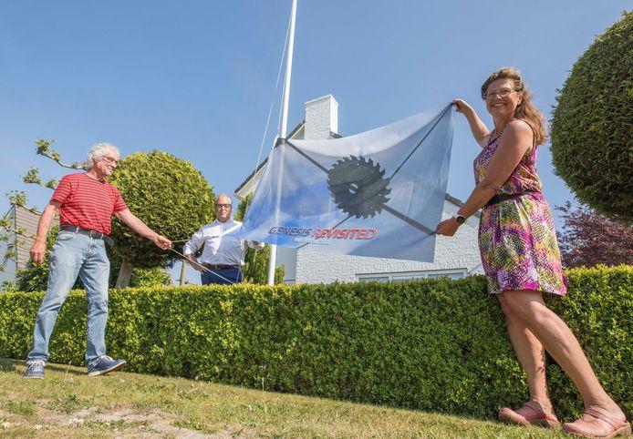 Kunstenaar Wim Bakker, bewoner André van der Reest en bedenkster Iris van 't Bos hijsen de eerste vlag.