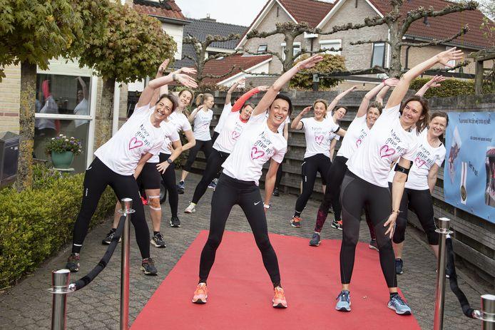 De warming-up van de zeventien loopsters van de halve marathon tegen kanker in Vriezenveen met de initiatiefneemsters Judith Scherphof  en Cobi van der Velde (respectievelijk links en rechts vooraan).
