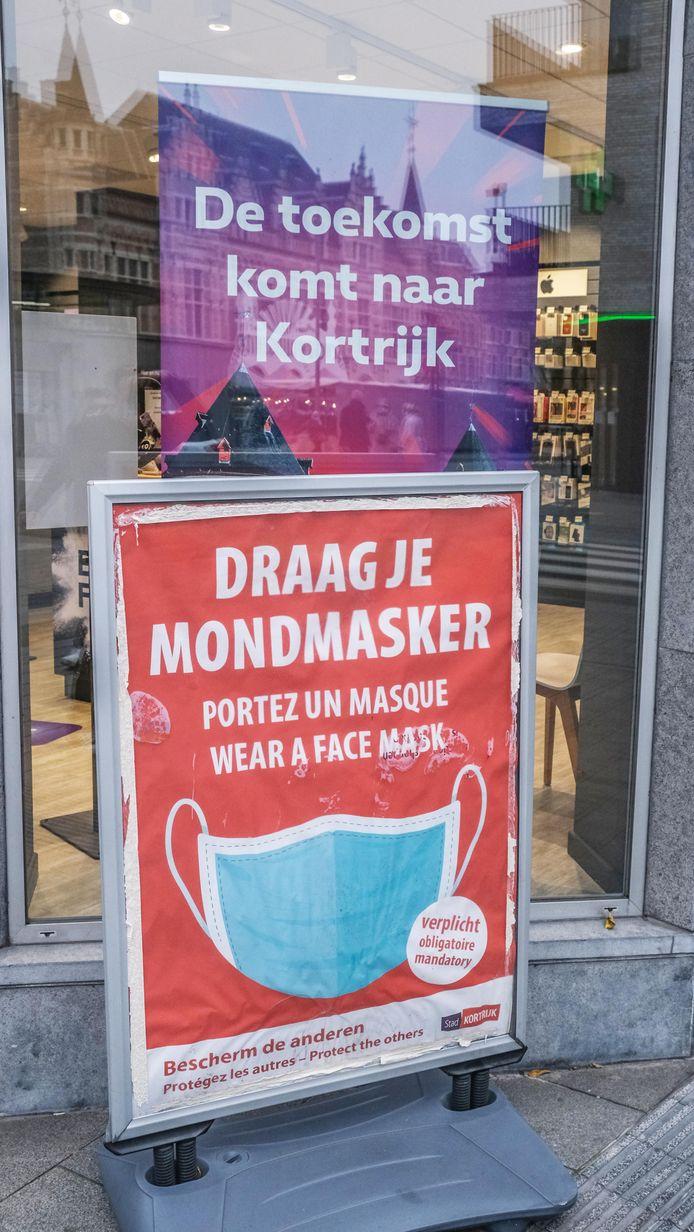 In de straat herinneren borden shoppers aan de verplichte mondmaskerdracht.