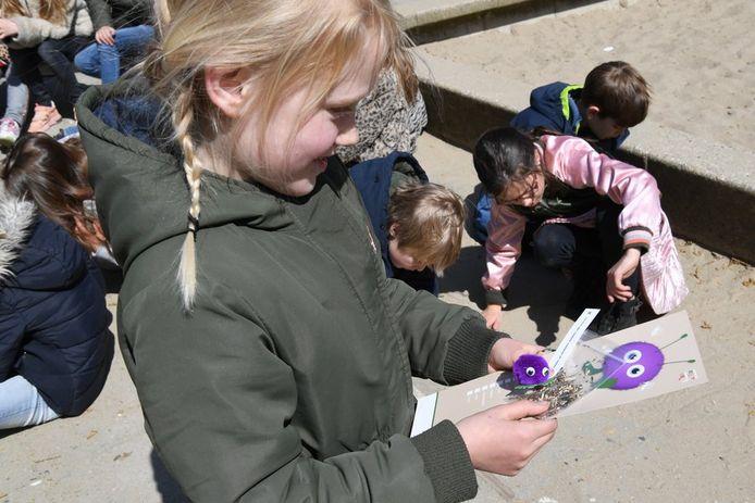Op de St Antoniusschool in Klein-Zundert bestudeert één van de kinderen het pakketje 'Tegel eruit, plantje erin' dat de gemeente en het Vogelrevalidatiecentrum verspreidden onder de groepen vijf en zes