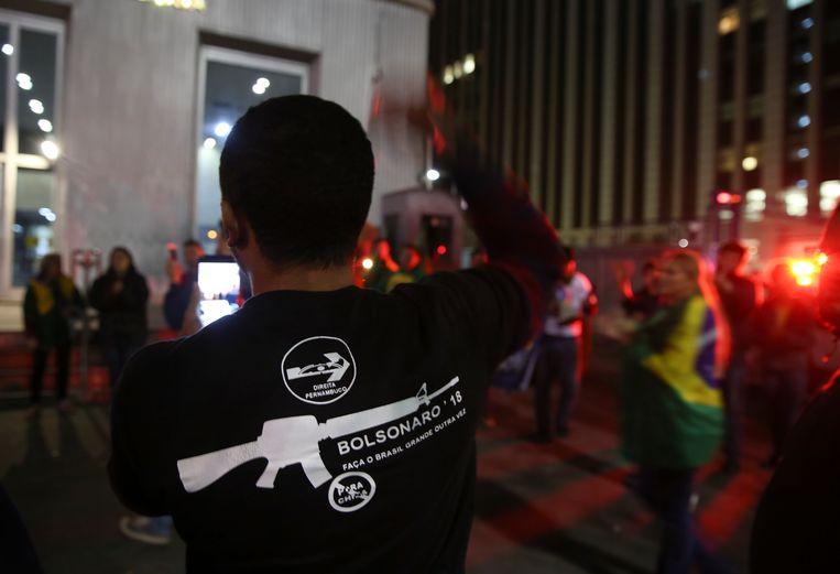 Een aanhanger van Bolsonaro met op zijn T-shirt de tekst 'Bolsonaro, maak Brazilië weer groot' schreeuwt steunbetuigingen voor de neergestoken politicus. Beeld AP