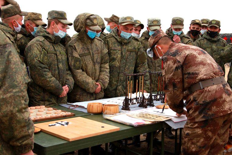Een Chinese soldaat demonstreert Chinese kalligrafie bij een gezamenlijke militaire oefening voor 'Peace Mission 2021' in Orenburg, Rusland, 17 september.  Beeld Getty