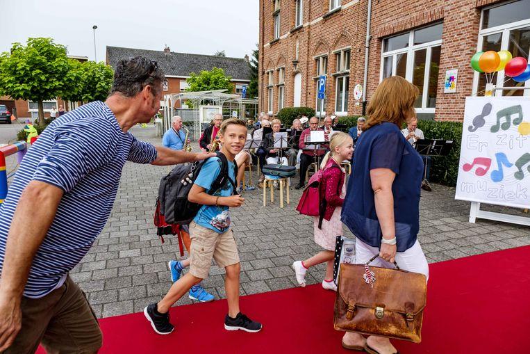 Een vader geeft zijn zoon nog vlug een schouderklop wanneer hij de school binnengaat.