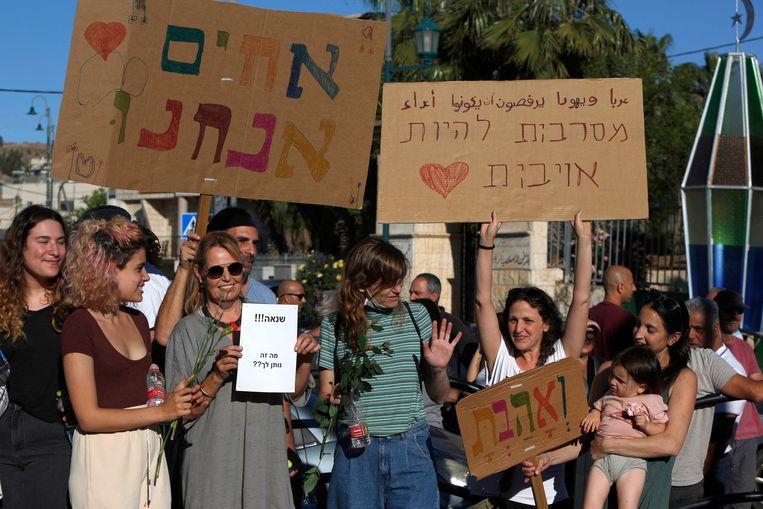 Demonstranten houden in het noorden van Israël op 13 mei protestborden op met de Hebreeuwse tekst: 'Wij zijn broeders' en 'Arabieren en Joden weigeren vijanden te zijn'   Beeld AFP
