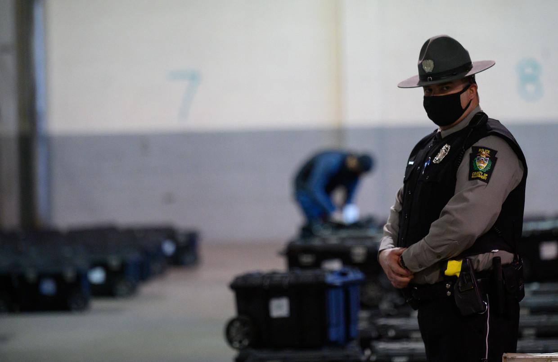 Een agent in Michigan bewaakt koffers met poststembrieven. Beeld Getty Images