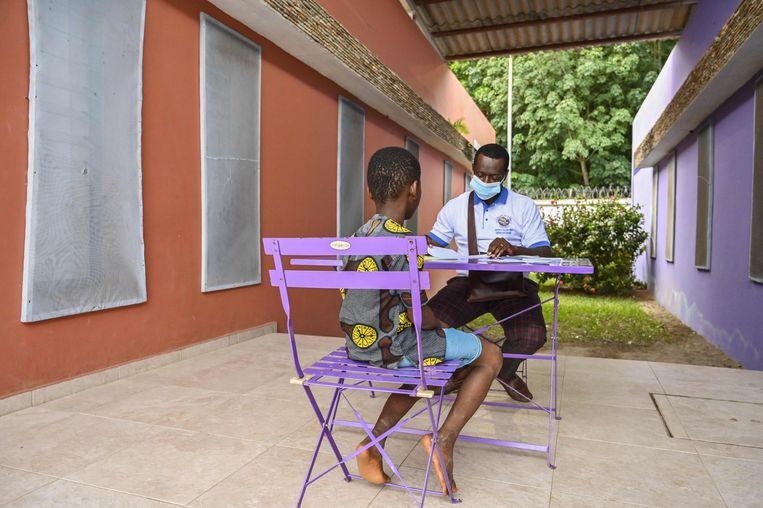Een sociaal werker luistert naar het verhaal van een kind dat tewerkgesteld werd op een cacaoplantage op Ivoorkust. Beeld AFP