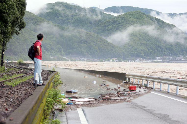 Een man kijkt naar de Kuma-rivier in Yatsushiro, in het zuidwesten van Japan Beeld Hollandse Hoogte / EPA