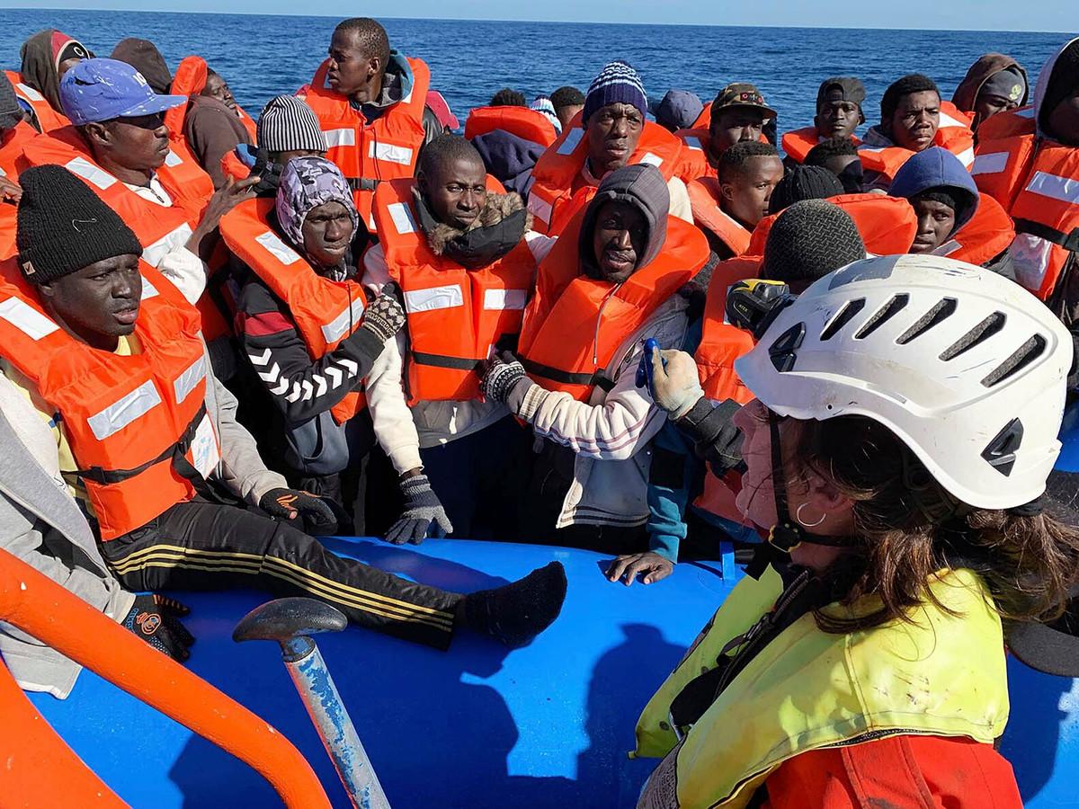 Geredde migranten met reddingswerkers van de Sea Watch 3 in de Middellandse Zee zaterdag.