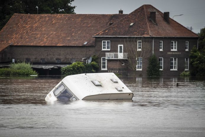 Een caravan drijft voorbij in het hoge water van de Maas in Roermond. Dit weekend komt het hoge water aan in Brabant.