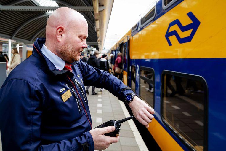 Een NS-conducteur met een smartwatch, sinds 2019 in gebruik om treinen op de seconde nauwkeurig te laten vertrekken. Tussen Amsterdam en Schiphol moet het nóg sneller, stelt de NS-directie. Beeld ANP