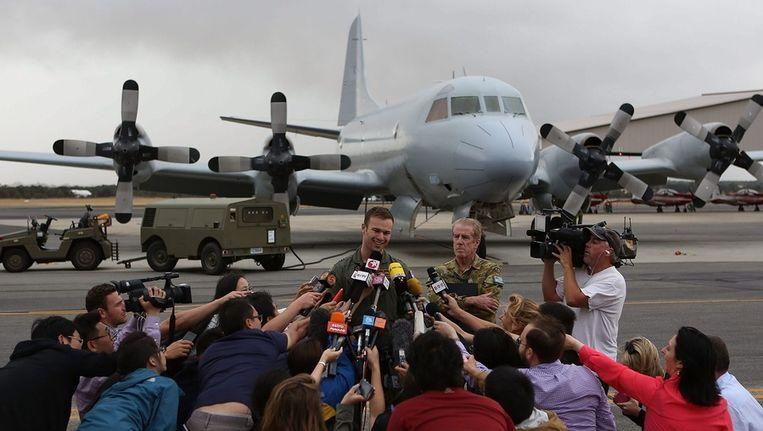 Luitenant Russell Adams van het Australische legervliegtuig dat de oranje objecten heeft zien drijven, staat de media te woord. Beeld EPA