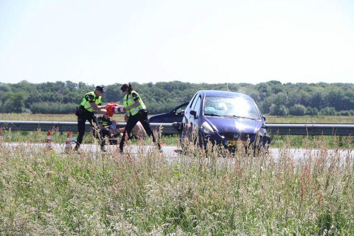 Agenten zetten de weg af. Op de achtergrond wordt eerste hulp verleend aan de vrouw die gewond raakte bij de aanrijding.