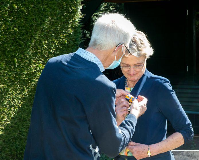 Marga van Weelden krijgt de onderscheiding opgespeld.