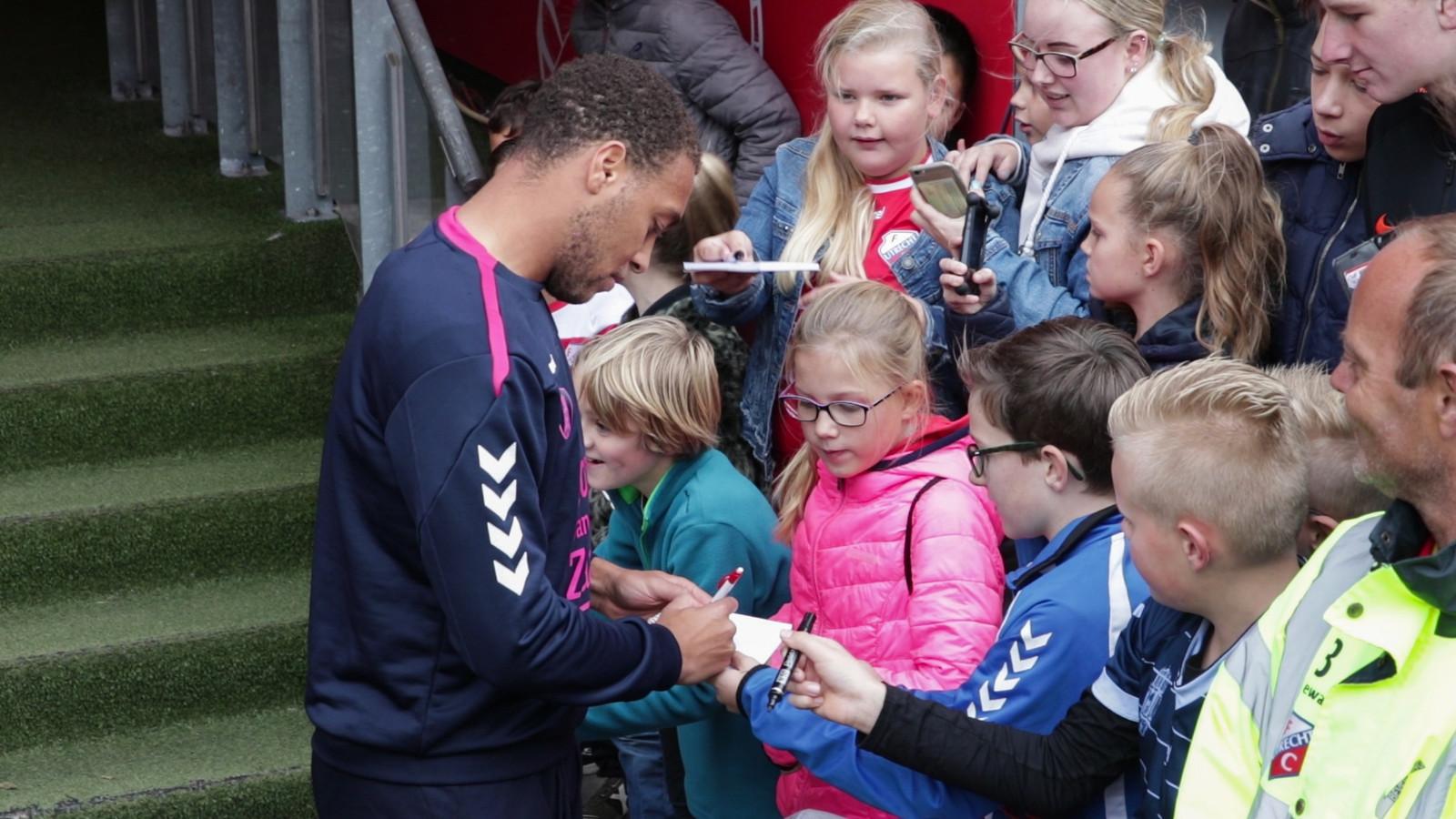 Jonge voetbalfans op jacht naar handtekeningen van hun idolen.