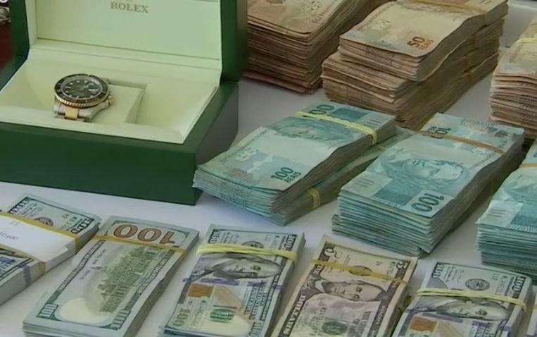 Een van de in beslag genomen Rolex-horloges en cash geld. Beeld Polícia Civil/Goiás