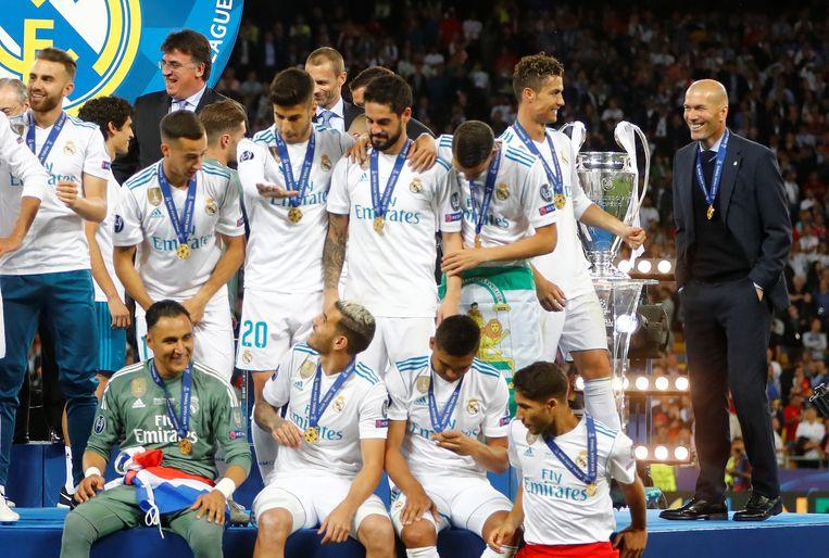 Terwijl de spelers hun medailles bewonderen, houden Ronaldo en Zidane een onderonsje vlakbij de beker met de grote oren. Beeld REUTERS