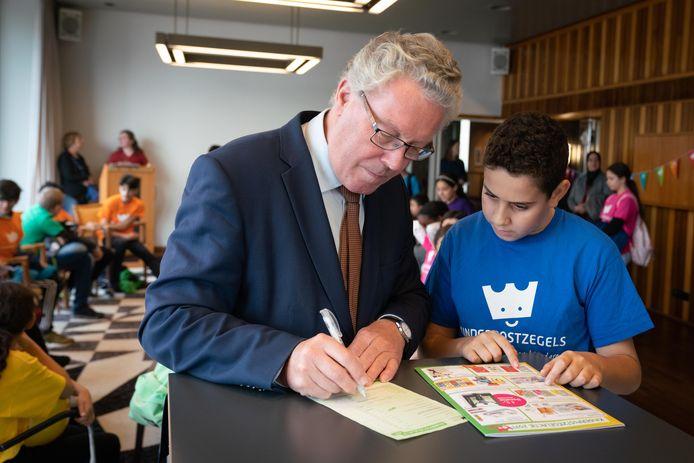 Kinderen van basisschool Het Mozaïek verkopen kinderpostzegels op het Provinciehuis: gedeputeerde Jan Markink en Rayan (11).