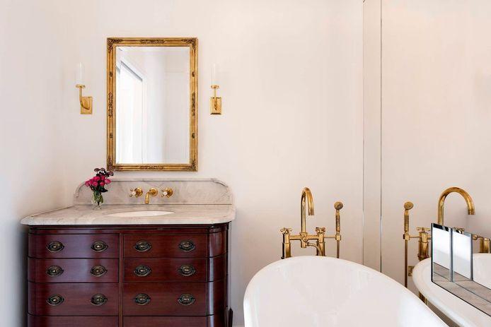De gouden kranen en het donker hout van het kastje  zorgen voor een klassieke touch.