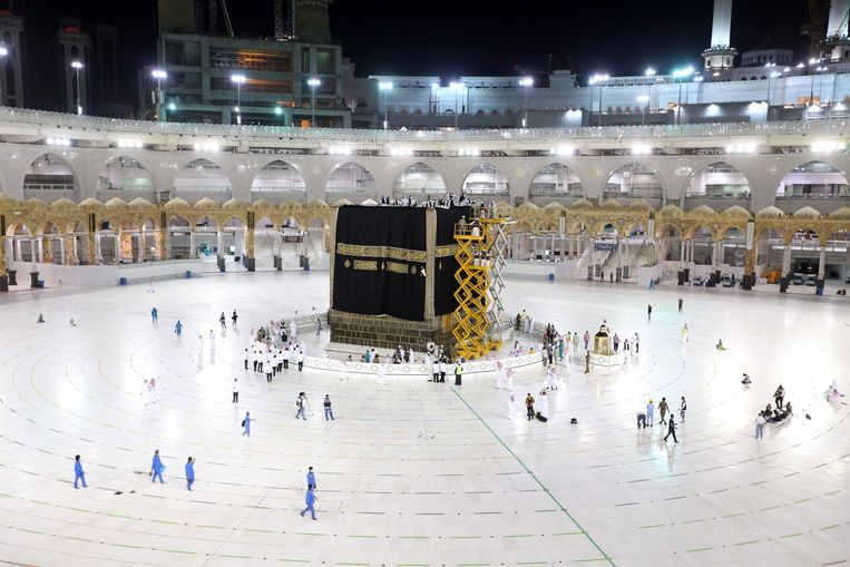 Saudi labourers put the new Kiswa, the protective cover that engulfs the Kaaba, made from black silk and gold thread and embroidered with Koran verses, on July 29, 2020 in Saudi Arabia's holy city of Mecca. - The drape which engulfs the Kaaba is formally called Kiswa and is changed every year at the culmination of the annual hajj, or pilgrimage, when the hajjis have left Mecca to go to Arafat, the starting point of their hajj journey. (Photo by - / AFP) Beeld AFP