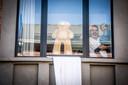 Jo Peters met zoontje Manil van achter hun raam