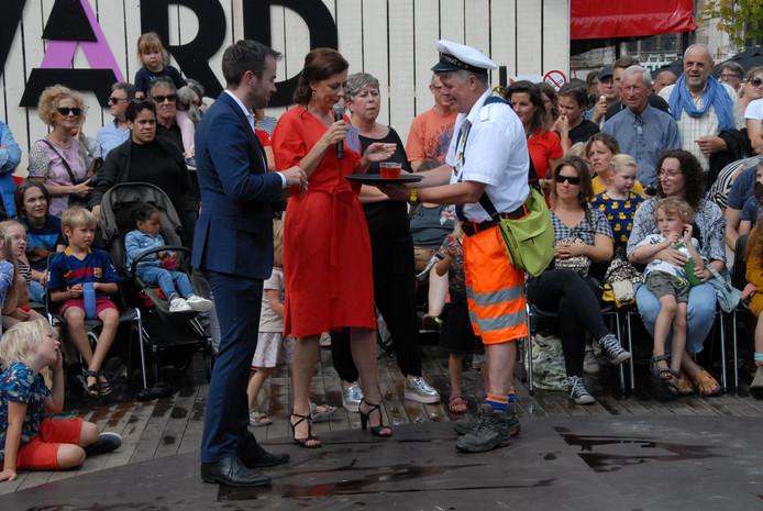 Wethouder Mike van der Geld en festivaldirecteur Viktorien van Hulst krijgen een welkomsdrankje aangeboden van 'Frits'