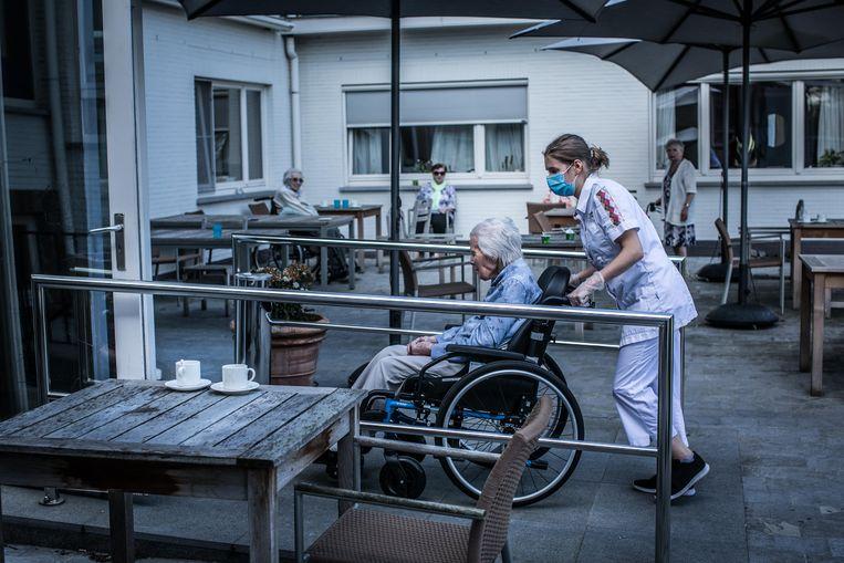 Rusthuisbewoners halen frisse lucht op het terras van woonzorg-centrum Orelia Ten Berge in Belsele. Beeld Bas Bogaerts