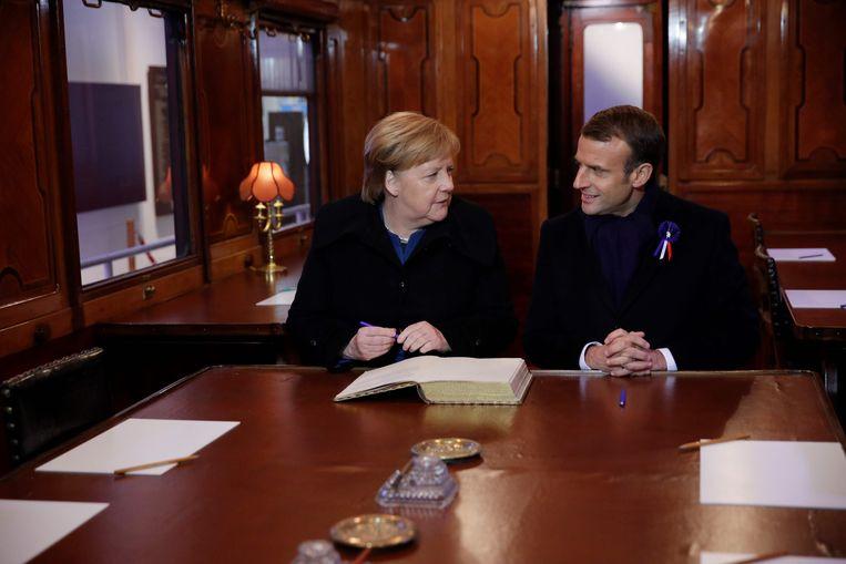 Angela Merkel en Emmanuel Macron brachten een kort bezoek aan de replica van de treinwagon waar in 1918 een einde aan WOI werd gemaakt. Beeld AFP
