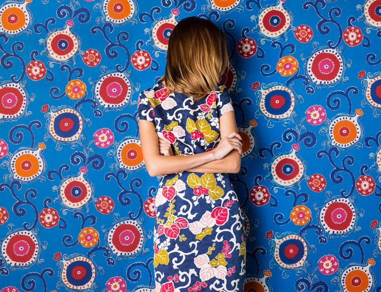 Beautiful young woman wearing blue floral, leaf print dress against blue, red, and orange floral print background with her hair hiding her face Beeld Getty Images