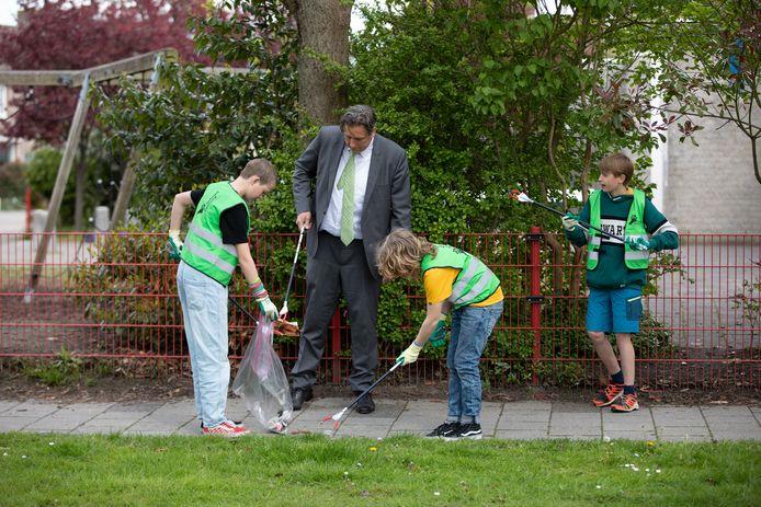 Kinderen van de Montessorischool ruimen afval op met wethouder Cees Pille.