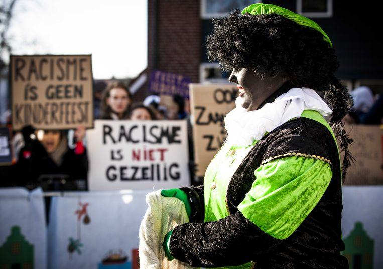 Demonstranten en een Zwarte Piet tijdens de landelijke intocht van Sinterklaas op de Zaanse Schans. De oer-Hollandse Zaanse Schans is dit jaar het decor van de landelijke intocht van de goedheiligman en zijn pieten. Beeld ANP